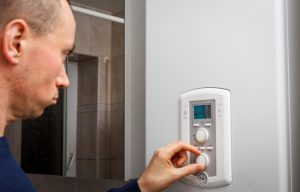 Men regulate temperature on control panel of central heating or DHW at combi boiler in restroom.