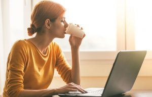Woman drinking coffee using laptop to illustrate story on social media security